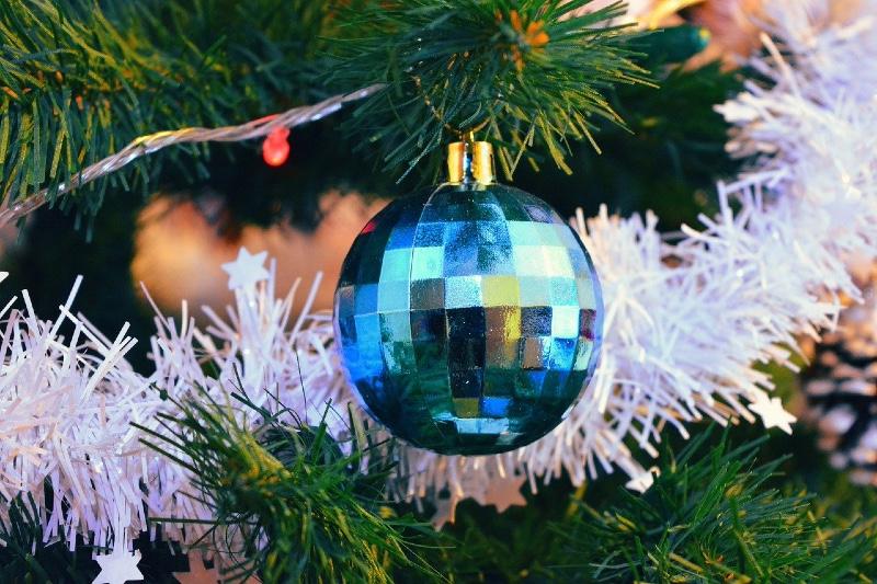 Künstlicher geschmückter Weihnachtsbaum mit einer Spiegellkugel.